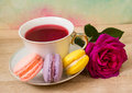 Hot cup of tea, colored cakes and pink flower Royalty Free Stock Photo