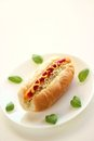 Hot dog with basil on white plate Royalty Free Stock Image