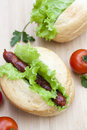 Hot dog. Grilled hot dogs with fresh salad lettuce on wooden table. Royalty Free Stock Photo