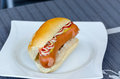 Hot dog with ketchup and mustard in bread roll on a white plate Stock Image