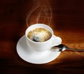 Hot fresh coffee in a white cup with spoon on wooden table Royalty Free Stock Images