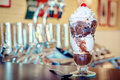 Hot fudge sundae with whipped cream and cherry with soda fountain in the background Stock Image