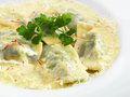 Hot healthy vegetarian ravioli with spinach and ricotta delicious under melted parmesan cheese on a round plate isolated on white Royalty Free Stock Images