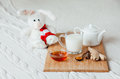 Hot milk in a glass cup and honey on  wooden board. Treatment of children   drink.   folk remedies in bed. Soft toy Royalty Free Stock Photo