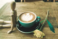 Hot mocha coffee or capuchino in the green cup lean by wood man on the wooden table