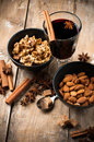 Hot mulled wine spices and nuts a glass of cinnamon star anise brown sugar on a wooden board Royalty Free Stock Images