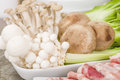 Hot pot ingredients thinly sliced beef prawns mushrooms tofu puff and green leaf vegetables Stock Image