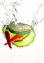 Hot salad two chilis and three slices of cucumber falling together into water studio isolated Stock Images
