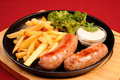 Hot sausages and fried potatoes Royalty Free Stock Photos