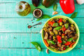 Hot spicy stew eggplant, sweet pepper, olives and capers with basil leaves. Royalty Free Stock Photo