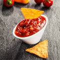 Hot spicy tomato and chili salsa sauce bowl of delicious served with triangular corn tortillas on a slate surface as a snack Stock Photography