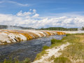 Hot spring flowing into river water in yellowstone national park Stock Photo