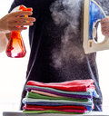 Hot steam iron man spraying water against a over a pile of colourful clothes creating clouds of Stock Photography