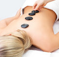 Hot stone massage in the day spa Stock Photos
