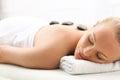 Hot stone massage, a woman in spa salon Royalty Free Stock Photo