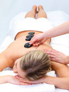 Hot stone massaging with hands Stock Image