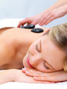 Hot stone massaging with hands - smiling face Royalty Free Stock Photos