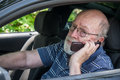 Hot sweaty senior man calls for roadside assistance closeup of elderly in car calling on cell phone he looks and miserable Royalty Free Stock Photos