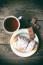 Hot tea with croissant and chocolate. Retro style image Royalty Free Stock Photo