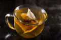 Hot tea cup of served on a dark setting with steam and an anise star floating with the bag Stock Image