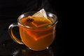 Hot tea cup of served on a dark setting with steam and an anise star floating with the bag Royalty Free Stock Images