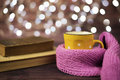 Hot tea, hot chocolate, coffee in yellow cup, wrapped with a pink knitted scarf.  Old books. Blurred lights, wooden background. Royalty Free Stock Photo