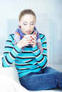 Hot tea sick woman in sweater and scarf holding cup with Stock Image