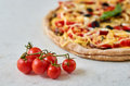 Hot vegetarian pizza with tomatoes, bell pepper, onion, black olives, cheese, spices on blurred white background close up Royalty Free Stock Photo
