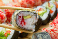 Hot or warm sushi roll takusen in tempura with red tobiko avocado and rice chopsticks with made dish on background Stock Images