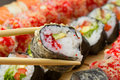 Hot or warm sushi roll takusen in tempura with red tobiko avocado and rice chopsticks with made dish on background Stock Photo