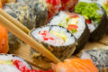 Hot or warm sushi roll takusen in tempura with red tobiko avocado and rice chopsticks with made dish on background Royalty Free Stock Photos