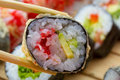 Hot or warm sushi roll takusen in tempura with red tobiko avocado and rice chopsticks with made dish on background Royalty Free Stock Photo