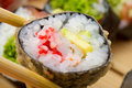 Hot or warm sushi roll takusen in tempura with red tobiko avocado and rice chopsticks with made dish on background Stock Image