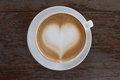 Hot white cup of coffee with heart shape on wood table from top view Royalty Free Stock Photo