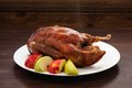 Hot whole roasted duck with fresh apples on wooden table