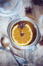 Hot winter drink herbal tea with orange and star anise in a vintage glass jar on a rustic wooden table Royalty Free Stock Photo