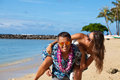 Hot young couple having a good time on a beach handsome male carrying female piggyback style the hawaiian playful love feeling and Stock Image