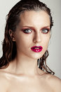 Hot young woman model with sexy bright red lips makeup strong eyebrows clean shiny skin and wet hairstyle beautiful fashion Royalty Free Stock Image