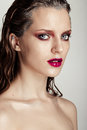 Hot young woman model with sexy bright red lips makeup strong eyebrows clean shiny skin and wet hairstyle beautiful fashion Stock Image