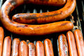Hotdogs sizzling on the outdoor grill cooking barbeque Stock Photography
