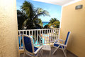 Hotel balcony overlooking the swimming pool palm trees and beautiful sea Royalty Free Stock Photos