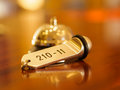 Hotel bell and key lying on the desk Royalty Free Stock Photo