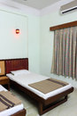Hotel or motel room interior of a simple and plain with double beds and air conditioner installed on the wall neat arranged and Royalty Free Stock Photo