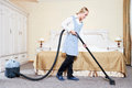Hotel service. female housekeeping worker with vacuum cleaner Royalty Free Stock Photo