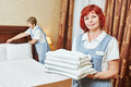Hotel staff at room cleaning and housekeeping service female worker with towels in front of maid making bed in Stock Photo