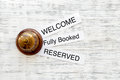 At the hotel. Words welcome, fully booked, reserved on light wooden table top view copyspace