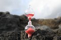 Hourglass abandoned time concept on the volcanic rocks Stock Photo