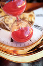Hourglass against the background of usual dial Stock Photos