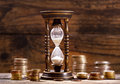 Hourglass and coins on wooden background Royalty Free Stock Photo