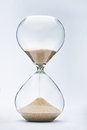 Hourglass with sand falling on white background Royalty Free Stock Photography